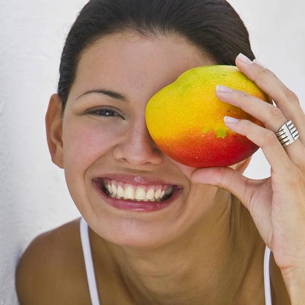 Girl holding mango over eye landscape.jpg Масло манго: применение и полезные свойства